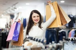 Portrait of happy female buyer with shopping bags at clothing store