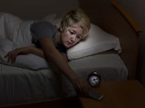 Teenage girl reaching for her cell phone, on night stand, while in bed. Teen using technology late at night instead of sleeping.