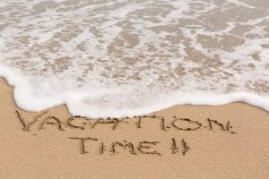 Vacation Time written in sand with sea surf